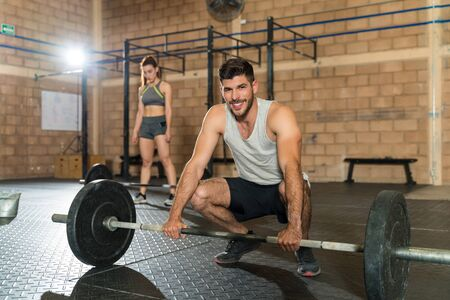 Smiling young Hispanic athletic male crouching with barbell at gym 版權商用圖片