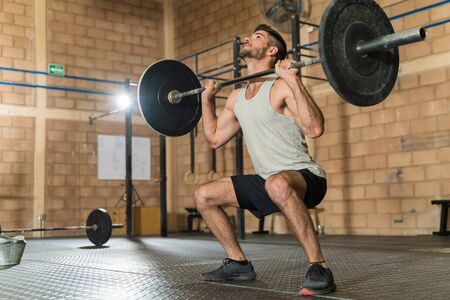 Strong sporty athletic male lifting barbell while looking up at gym during strength training