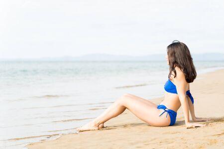 Frau mit Bikini am Ufer entspannen, während sie im Sommer Meereswellen genießt Standard-Bild