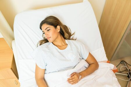 High angle view of thoughtful sick patient looking away while lying on hospital bed during treatment