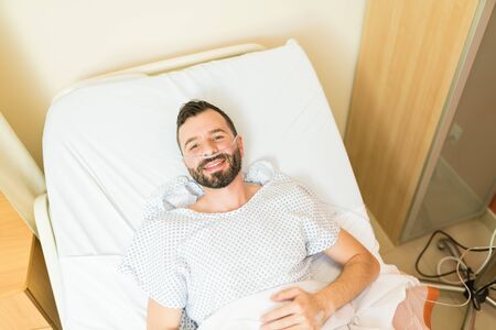 High angle view of smiling mid adult patient lying on hospital bed during treatment and smiling