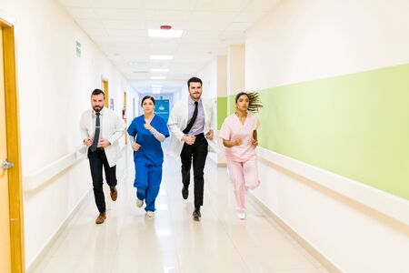 Worried male and female doctors and nurses running in corridor at hospital during emergency