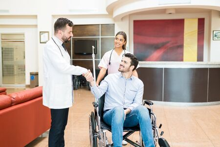 Hispanic man smiling on wheelchair while shaking hands with healthcare workers standing at hospital lobby  Imagens