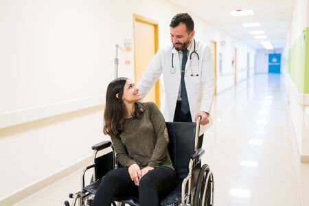 Mid adult doctor talking to discharged smiling young patient while pushing wheelchair at corridor in hospital
