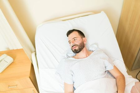 Thoughtful sick patient looking away while lying on hospital bed during treatment Stock Photo