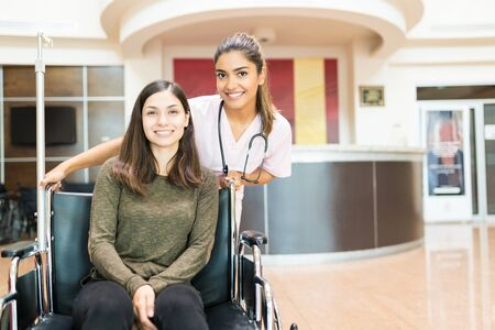 Smiling female orderly with young woman sitting on wheelchair at lobby in hospital