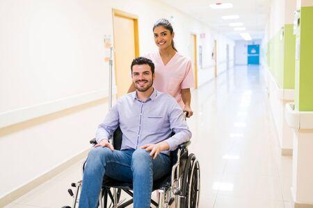 Sonriendo ordenado empujando al paciente adulto medio dado de alta en silla de ruedas en el pasillo del hospital