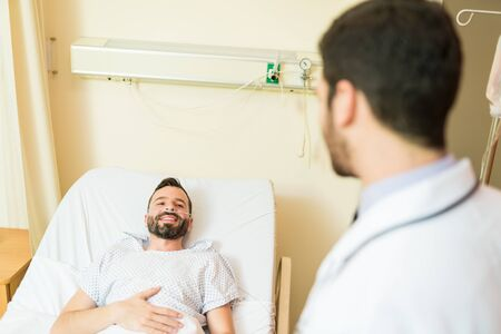 Sick mid adult patient looking at healthcare worker while lying on bed in hospital