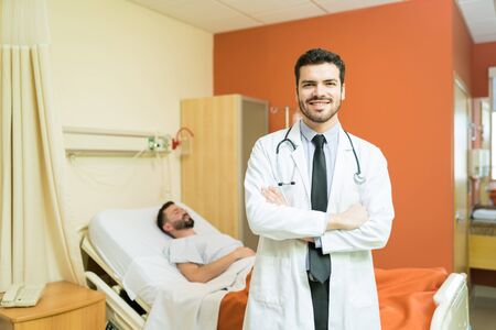 Smiling Hispanic healthcare worker with arms crossed standing against sick patient at hospital bed 免版税图像