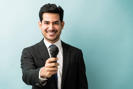 Happy good looking male professional in suit giving microphone while standing in studio