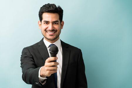 Heureux beau professionnel masculin en costume donnant un microphone en se tenant debout en studio