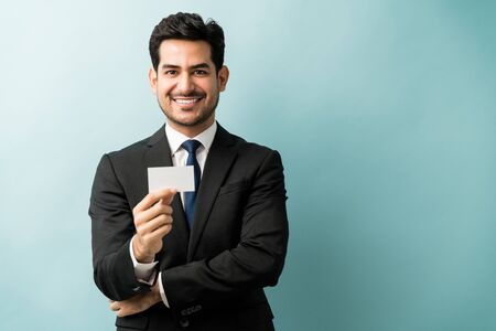 Smiling handsome businessman holding blank business card while standing against blue background