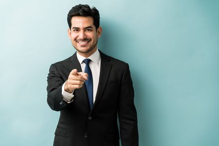 Confident good looking young businessman pointing finger while standing against isolated background Stock fotó