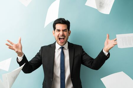 Aggressive young male entrepreneur shouting while throwing documents in studio