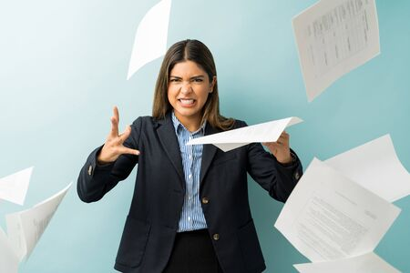 Aggressive young female entrepreneur throwing documents against blue background 版權商用圖片