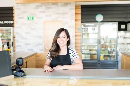 Portrait of female caissier à la caisse en supermarché Banque d'images