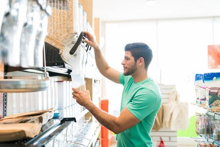 Side view of Hispanic male customer pouring food into container and buying in bulk at store