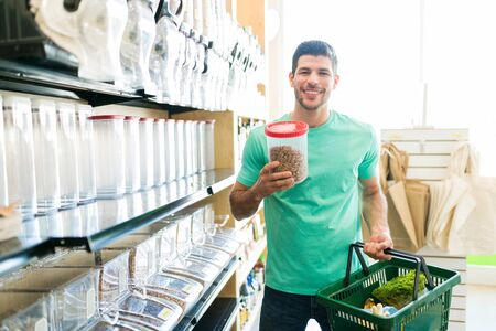 Smiling male customer holding pecan container and vegetable basket in grocery store