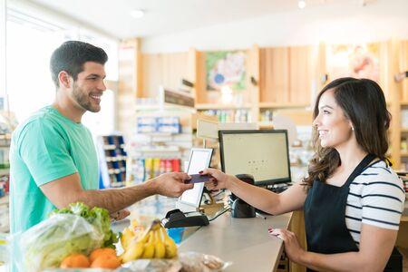 Cajero femenino sonriente con el comprador en el mostrador de la caja en la tienda de comestibles