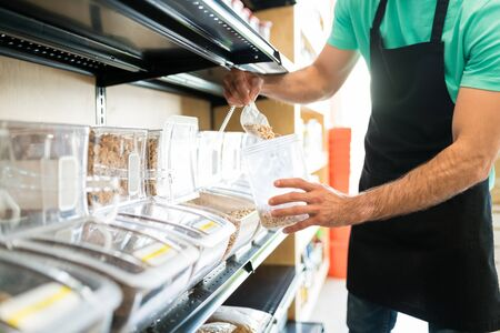 Midsection of Latin male owner putting food in container at grocery store