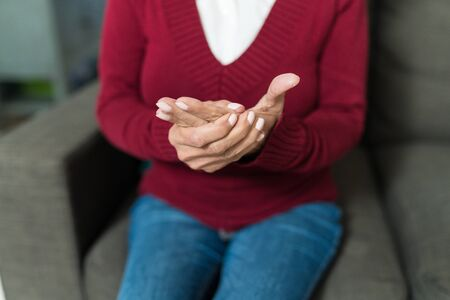 Midsection of senior woman massaging hand while sitting on sofa