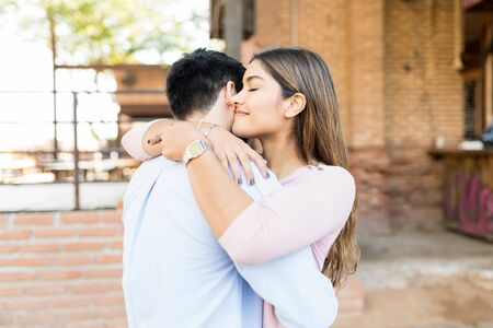 Smiling girlfriend embracing boyfriend outside cafe