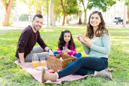 Uśmiechnięta rodzina jedząca i pijąca siedząc razem na pikniku w parku Zdjęcie Seryjne