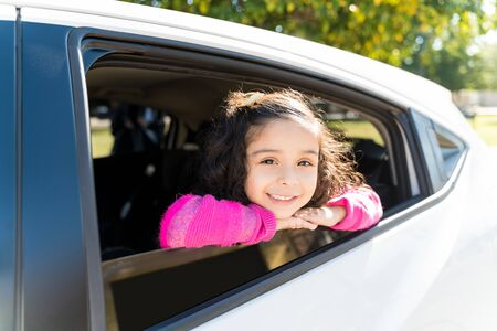 Smiling Girl Leaning On Car Window While Making Eye Contact During Sunny Day Stock Photo