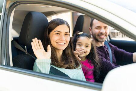 Mujer sonriente saludando mientras está sentado con su hija y el hombre en el coche Foto de archivo
