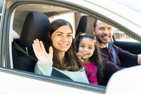 Smiling Woman Waving While Sitting With Daughter And Man In Car Banco de Imagens