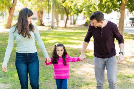 Sonriente madre y padre mirando a su hija mientras camina sobre el césped en el parque