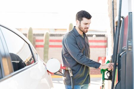 Male worker operating fuel pump machine at gas station