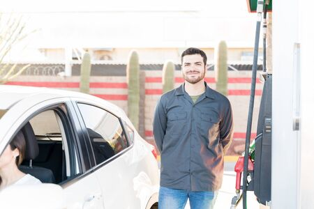 Confident male attendant standing by fuel pump at gas station