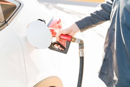 Midsection of male staff refueling car at gas station