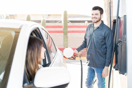 Confident male attendant talking with customer while tanking car at gas station