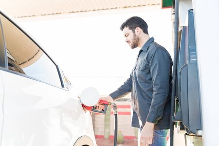 Side view of male worker in uniform refueling car at gas station