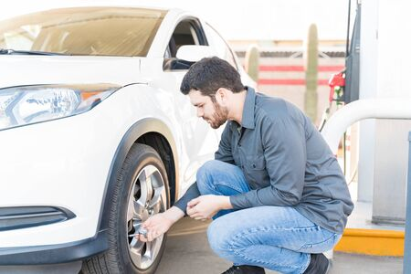 Vista lateral del asistente de la gasolinera masculino comprobando la presión del aire del neumático del automóvil