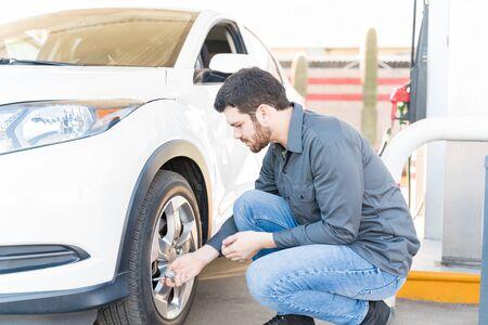 Widok z boku męskiego pracownika stacji benzynowej sprawdzającego ciśnienie powietrza w oponie samochodowej