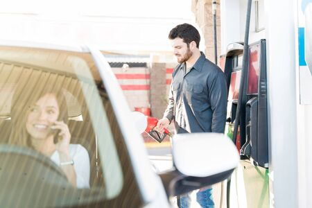 Male attendant refueling car while woman talking on mobile phone at gas station