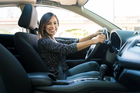 Side view of smiling Caucasian woman traveling in new car