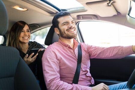 Glimlachende mannelijke chauffeur in gesprek met vrouwelijke passagier in auto