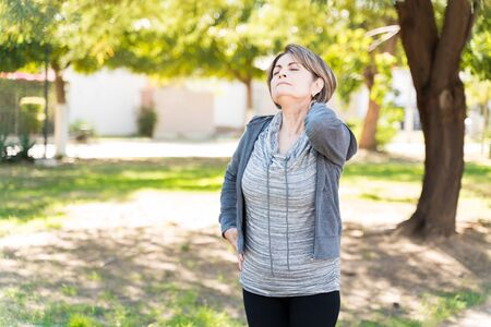 Senior woman with hand on neck grimacing from pain while standing with eyes closed in a park