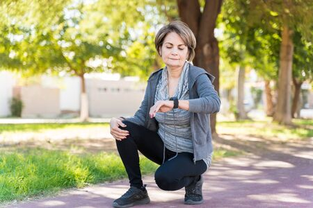 Confident elderly woman looking at smartwatch while crouching on sidewalk