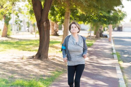 Active elderly Caucasian woman running on sidewalk while looking away in city