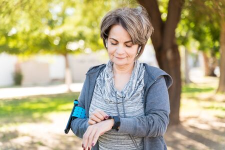 Confident retired senior woman looking at smartwatch on wrist in city