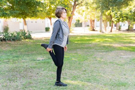 Full length of active woman stretching her leg while looking away at park