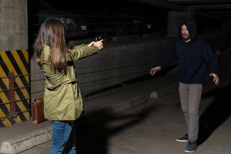Woman pointing gun at criminal standing in dark parking lot Standard-Bild
