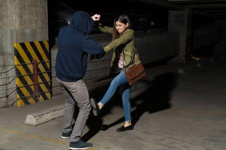 Full length of Latin woman fighting against robber in dark parking lot