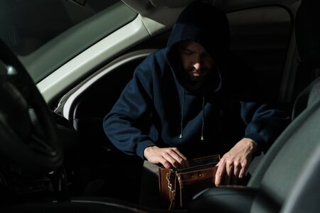 Latin male bandit stealing from purse in front seat of car at parking lot