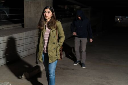 Unsuspecting beautiful young woman walking in front of thief at dark alley Standard-Bild